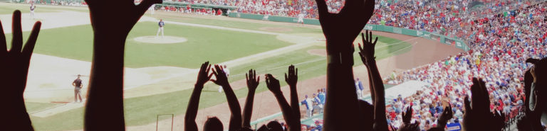 Photo of hands raised, cheering at a baseball game.